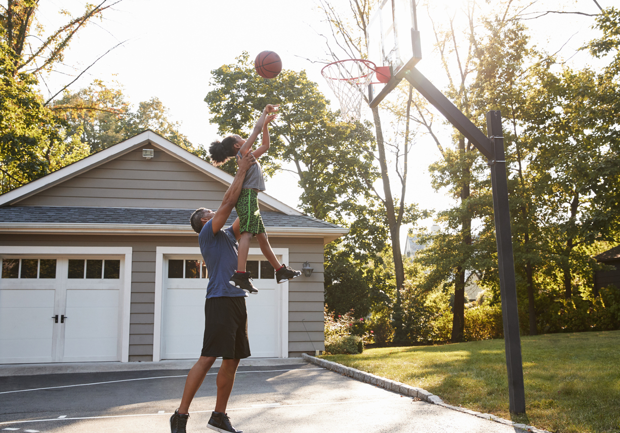 Father And Son Playing Basketball On Driveway At Home in Long Island, NY.